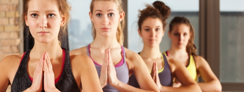 Young Women Practicing Tree Pose in Group Exercise Yoga Workout